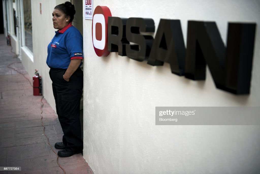 An employee stands near Grupo Orsan signage during the unveiling of an Exxon Mobil Corp. gas station in Santiago de Queretaro, Mexico, on Wednesday, Dec. 6, 2017. Exxon Mobil Corp. is joining Chevron Corp. and other U.S. refiners to supply the newly free Mexican fuel market. Exxon Mobil indicated Wednesday that it will open 50 service stations by the end of first quarter and invest more than $300 million in Mexico's energy sector. Photographer: Jonathan Levinson/Bloomberg via Getty Images