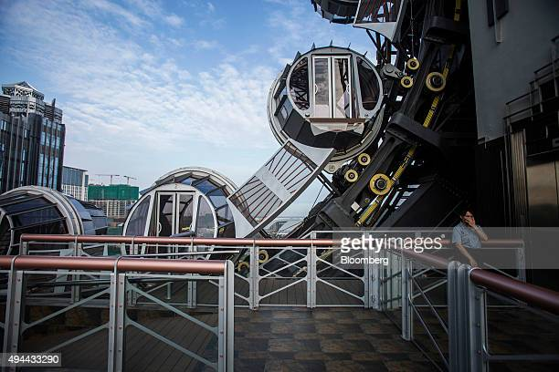 An employee stands near passenger pods at the Golden Reel ferris wheel at Studio City casino resort developed by Melco Crown Entertainment Ltd in...