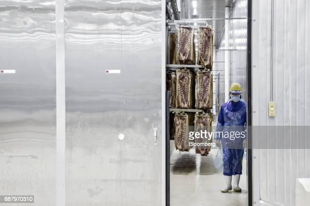 An employee stands near racks of imported Smithfield Foods Inc pork bellies which will be processed into bacon at the WH Group Ltd facility in...