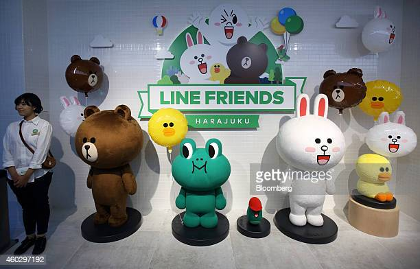 An employee stands next to a display of Line Corp characters at the Line Friends Store in Tokyo Japan on Thursday Dec 10 2014 Line which makes money...