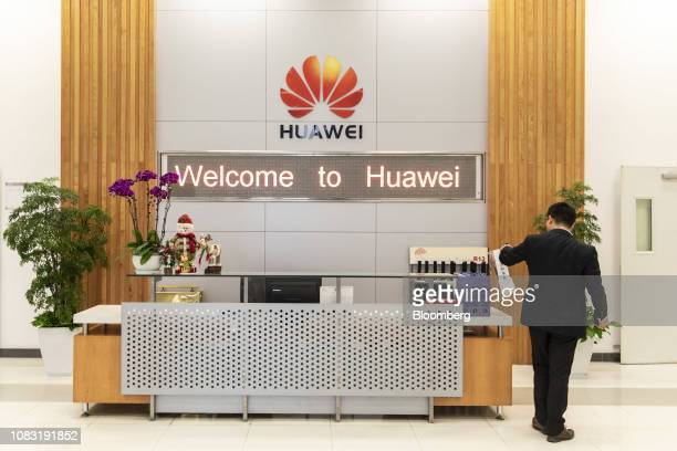 An employee stands next to a reception desk of a Huawei Technologies Co mobile phone plant in Dongguan China on Tuesday Jan 15 2019 Ren Zhengfei the...