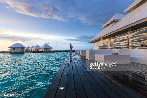 An employee stands next to an overwater restaurant on Athuruga island on May 27 2012 in Athuruga Maldives The Republic of the Maldives consists of...