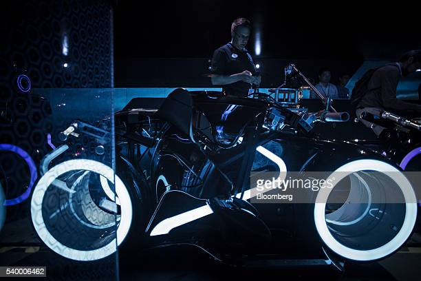 An employee stands next to the cars of the Tron Lightcyle Power Run rollercoaster at Walt Disney Co's Shanghai Disneyland theme park during a trial...
