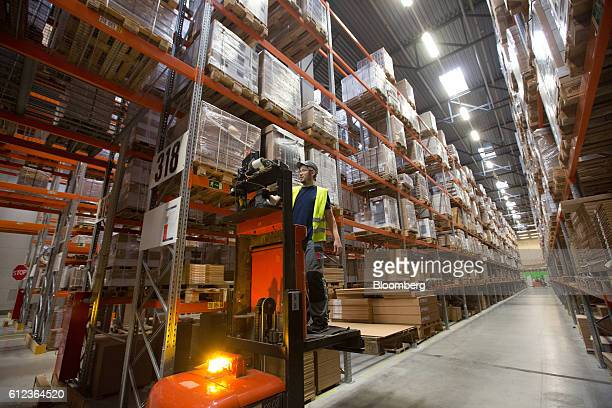 An employee stands on a forklift truck platform to access higher levels in a storage aisle at the Ikea AB distribution center in Yesipovo village...