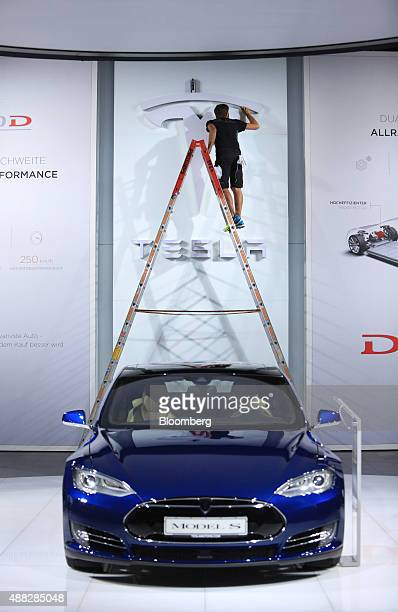 An employee stands on a ladder as he arranges the Tesla Motors Inc company's exhibition stand during previews to IAA Frankfurt Motor Show in...