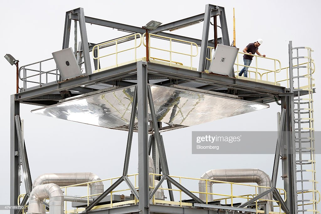 An employee stands on a raised platform of on a solar generation unit at a Solar Thermoelectric Magaldi (STEM) pilot plant, operated by Magaldi Group, in Buccino, Italy, on Monday, May 18, 2015. The project captures the energy of the sun which is transferred via the generation unit to heat retaining silica sand, producing steam that powers a turbine and is suitable for use in systems operating over a large temperature range. Photographer: Alessia Pierdomenico/Bloomberg via Getty Images
