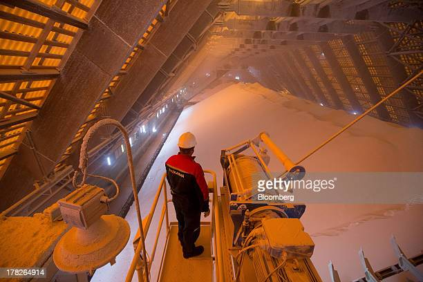 An employee stands on a sorting machine above stores of potassium chloride also known as potash at a storage plant operated by OAO Uralkali in...