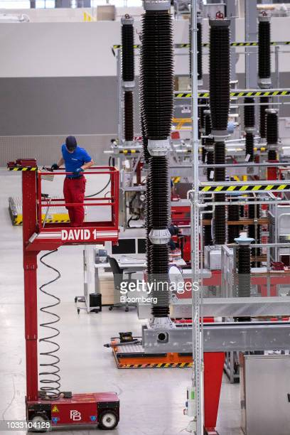 An employee stands on an elevated cherry picker platform on the live tank circuit breaker production line inside Siemens AG switchgear electronic...