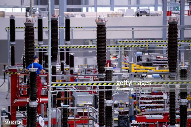 An employee stands on an elevated cherry picker platform while working on the live tank circuit breaker production line inside Siemens AG switchgear...