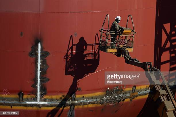 An employee stands on an elevated work platform beside a Seadrill Ltd semisubmersible drilling rig under construction in the dry dock at the Hyundai...