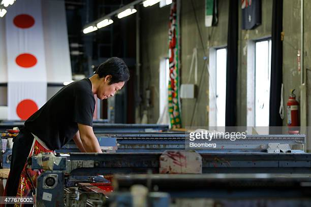 An employee stands over a printing screen while printing Japanese national flags at Tokyo Seiki Inc's manufacturing facility in Numata Gunma...