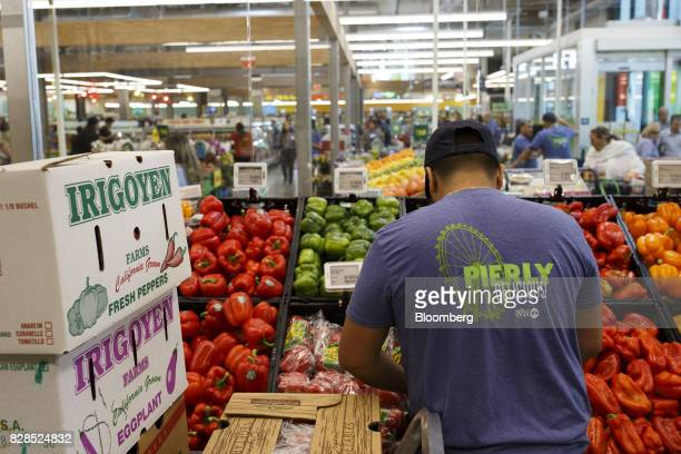 An employee stocks produce during the grand opening of a Whole Foods Market 365 location in Santa Monica California US on Wednesday Aug 9 2017 The...