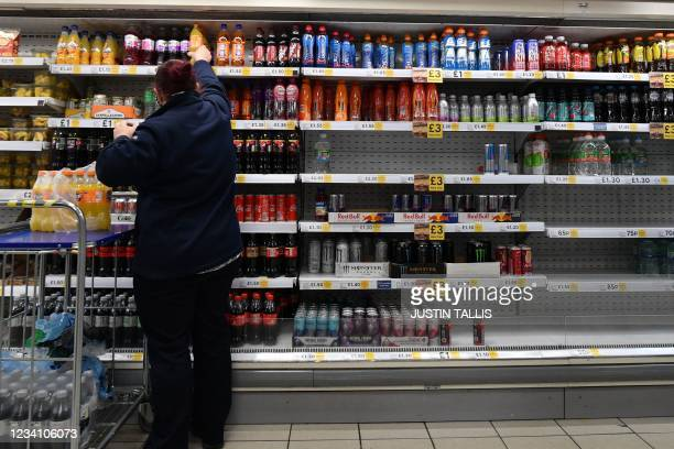 An employee stocks shelves at a Tesco supermarket in central London on July 22, 2021. - British supermarkets and suppliers warned today of possible...