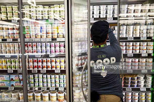 An employee stocks yogurt for sale on the opening day of the 365 by Whole Foods Market store in the Silver Lake neighborhood of Los Angeles...