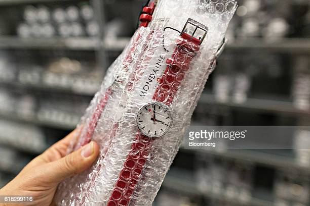 An employee stores packaged stop2go official Swiss Railways model wristwatches into the storage area at the Mondaine Watch Ltd production facility in...