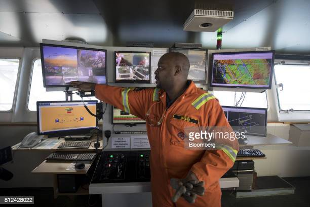 An employee studies digital monitors showing camera views of mooring systems in the operations room aboard the Mafuta diamond mining vessel operated...
