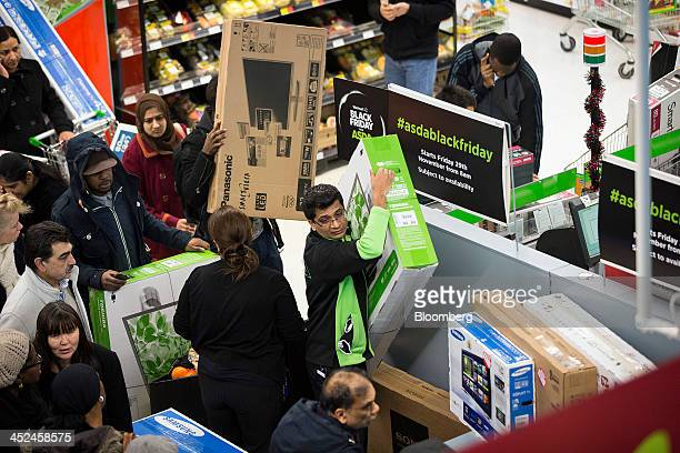 An employee surrounded by customers carries a new Toshiba Corp flat screen television during a Black Friday discount sale inside an Asda supermarket...