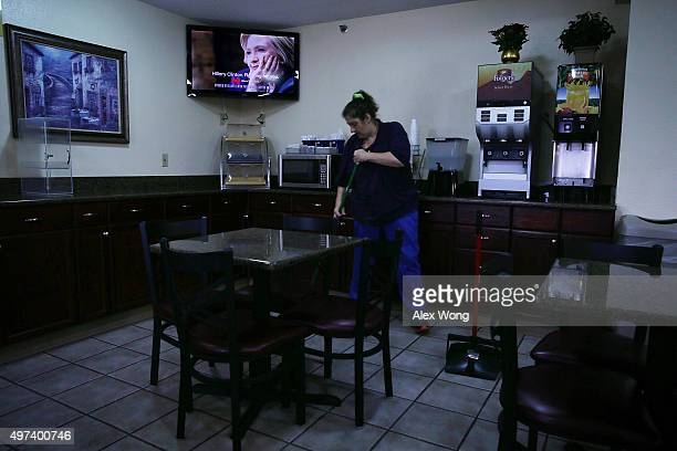 An employee sweeps the floor as a campaign ad paid for by Democratic presidential candidate Hillary Clinton's campaign is shown on the TV in a hotel...