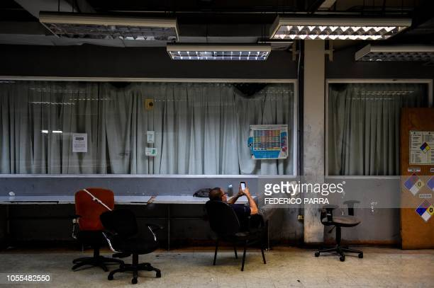An employee take a rest at the printing room of Venezuelan newspaper El Nacional in Caracas on October 5 2018 Surrounded by empty chairs a bunch of...