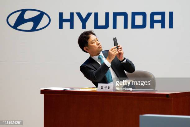 An employee takes a photograph during the Hyundai Motor Co annual shareholders meeting at the company's headquarters in Seoul South Korea on Friday...