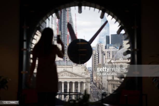 An employee takes a photograph of the view of London's business centre from a window at the WeWork, coworking and office space in the City of London,...