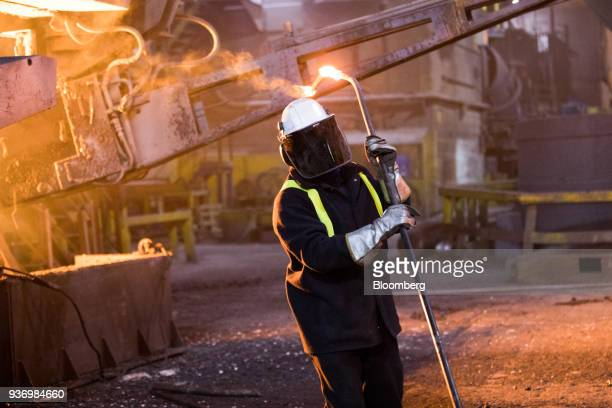 An employee takes a sample from the electric arc furnace at Liberty Steel's Aldewerke mill in Rotherham UK on Wednesday March 21 2018 Most metals...