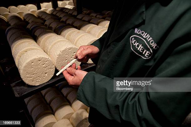 An employee takes a sample of Roquefort Societe 150years cheese from maturing racks in caves at the LebrouRoquefort plant part of Groupe Lactalis SA...
