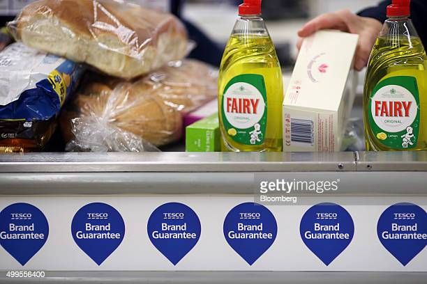 An employee takes an item from the conveyor belt at the Tesco Basildon Pitsea Extra supermarket operated by Tesco Plc in Basildon UK on Tuesday Dec 1...