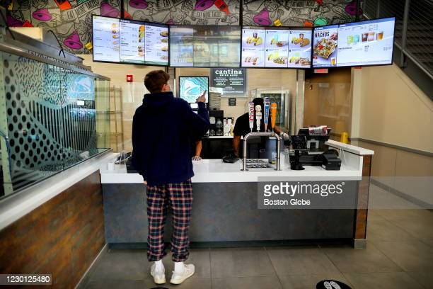 An employee takes an order at the new Taco Bell Cantina in Brookline, MA on Dec. 4, 2020. The new Taco Bell on Boston University's campus on...