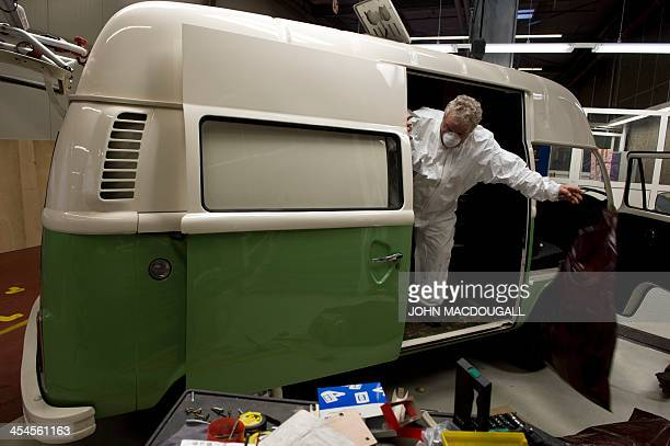 An employee takes apart the inside of a Volkswagen T2 aka kombi or bulli camping van preparing it for renovation at a Volkswagen workshop specialised...