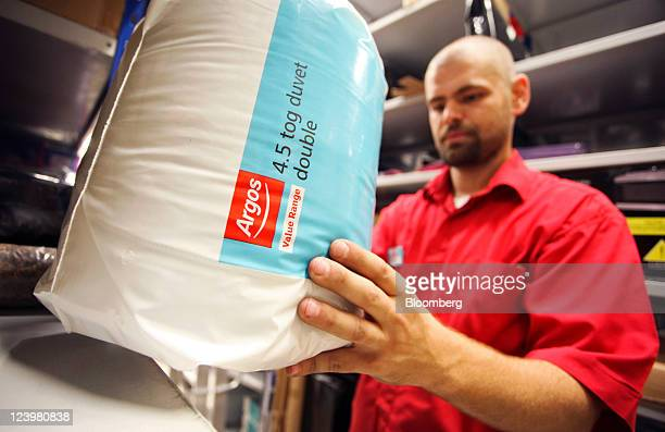 An employee takes Argosbranded duvet from the warehouse inside an Argos store operated by Home Retail Group Plc in Enfield UK on Wednesday Sept 7...