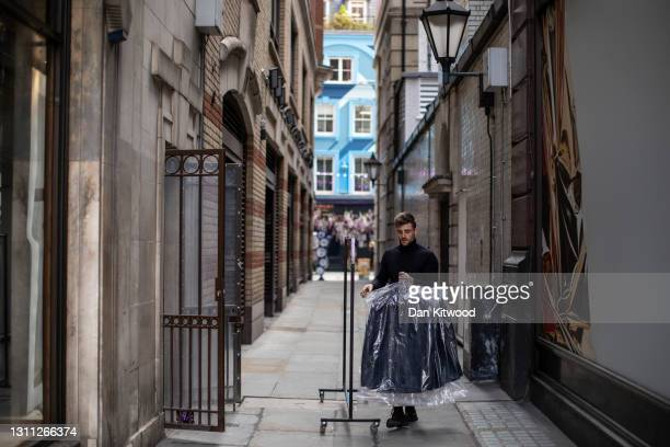 An employee takes new clothes into a store on Regent Street on April 07, 2021 in London, England. All non-essential retail will be able to reopen...