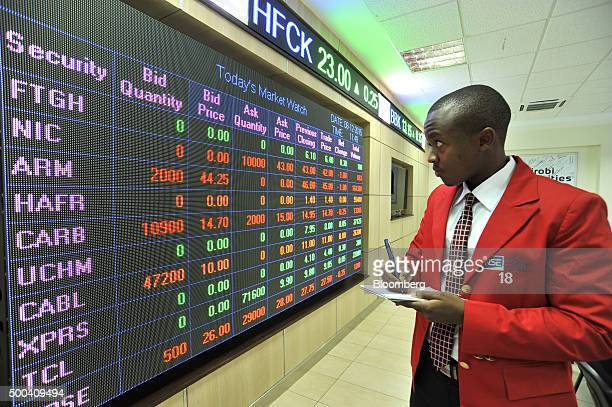 An employee takes notes of the latest stock prices displayed on an electronic screen inside the Nairobi Securities Exchange Ltd in Nairobi Kenya on...
