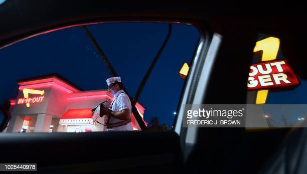 An employee takes orders from drivers waiting in the drivethru lane at an InNOut Burger restaurant in Alhambra California on August 30 2018...