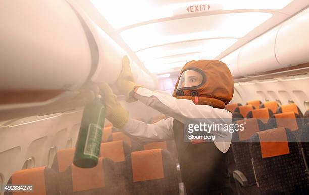 An employee takes part in a mock cabin fire exercise using a fire extinguisher at the opening of EasyJet Plc's new European training facility at...