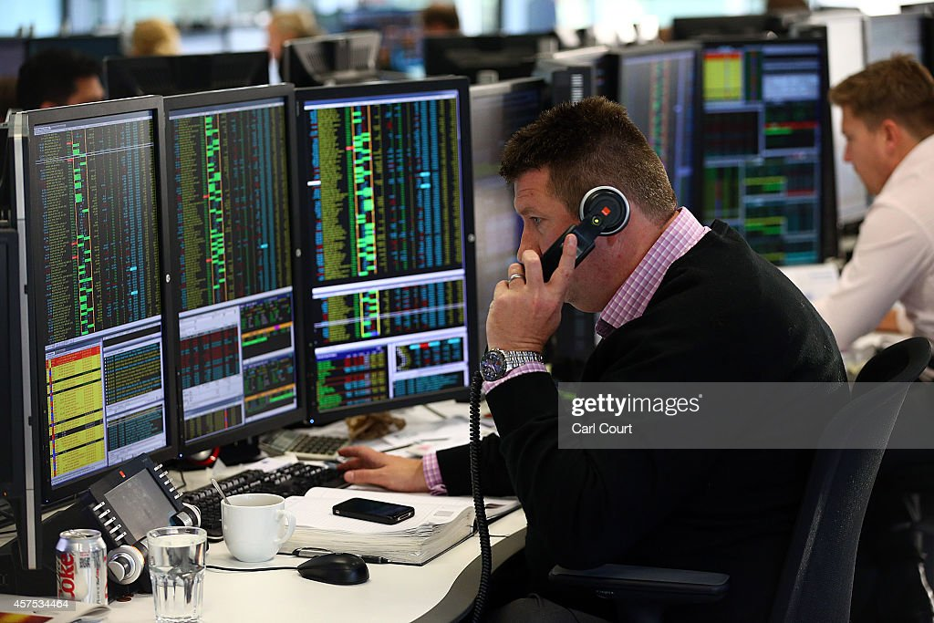 An employee talks on the phone as he views trading screens at the offices of Panmure Gordon and Co on October 20, 2014 in London, England. Markets stabilised over the weekend following global turbulence amid fears over the Ebola virus and global economic concerns.