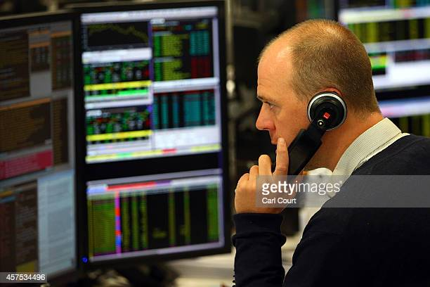 An employee talks on the phone as he views trading screens at the offices of Panmure Gordon and Co on October 20, 2014 in London, England. Markets...