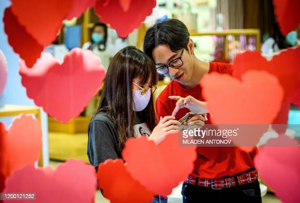 An employee talks to a woman wearing a protective facemask behind Saint Valentine's decorations in a shopping mall in Bangkok on February 11 2020 The...