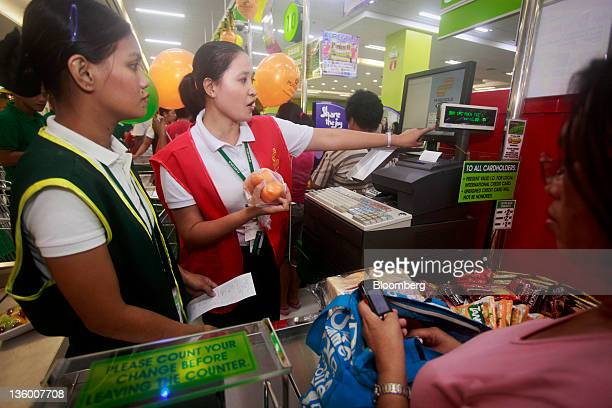 An employee tallies up purchases at a checkout counter of a newly opened Puregold Price Club Inc store in Manila the Philippines on Monday Dec 19...