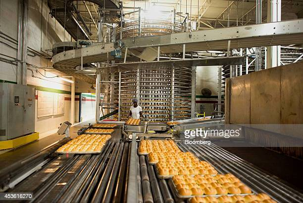 An employee taps the bottom of trays to to loosen the bread in pans at the Orlando Baking Co in Cleveland Ohio US on Wednesday Aug 13 2014 Wheat rose...