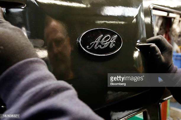 An employee tests a door plate for an AGA range cooker produced by AGA Rangemaster Plc during the manufacturing process at the company's plant in...
