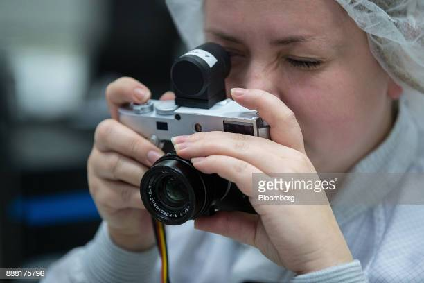 An employee tests an external electronic viewfinder on a Leica M10 rangefinder digital camera at the Leica Camera AG factory in Wetzlar Germany on...