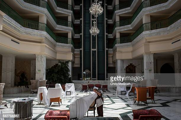 An employee throws sheets over lobby furniture at the closed Imperial Marhaba Hotel on June 24 2016 in Sousse Tunisia The Imperial Marhaba hotel was...