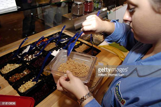 An employee tops off the cinnamon streusel container at Cereality Cereal Bar and Cafe December 1 2004 in Philadelphia Pennsylvania Cereality sells...