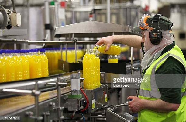 An employee tops up the content in a bottle of Robinsons orange fruit and barley squash drink produced by Britvic Plc as it moves along the...