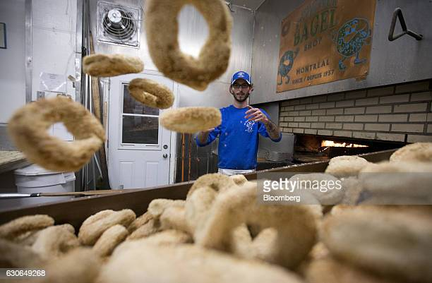 An employee tosses hand rolled bagels from the oven onto a counter at StViateur Bagel Shop in Montreal Quebec Canada on Monday Dec 26 2016 Bloomberg...