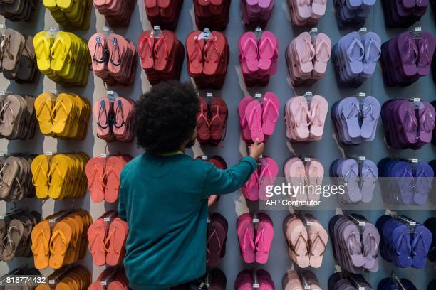 An employee touches a pair of Brazilian Havaianas flipflops at a store in Sao Paulo Brazil on July 18 2017 The Havaianas ambassadors of Brazil in the...