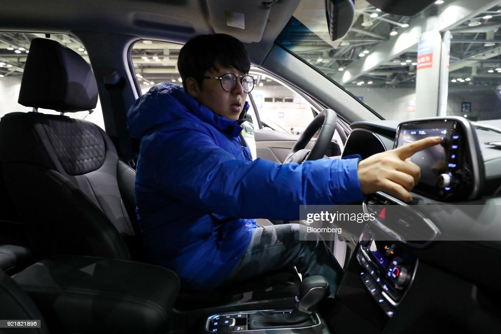 An employee touches a screen of a Hyundai Motor Co. Santa Fe sport utility vehicle (SUV) during a launch event for the updated vehicle in Goyang, South Korea, on Wednesday, Feb. 21, 2018. To recapture buyers in the U.S. who have shunned its sedans and compact cars, Hyundai has said it will bring eight new or redesigned crossovers or SUVs by 2020. Photographer: SeongJoon Cho/Bloomberg via Getty Images