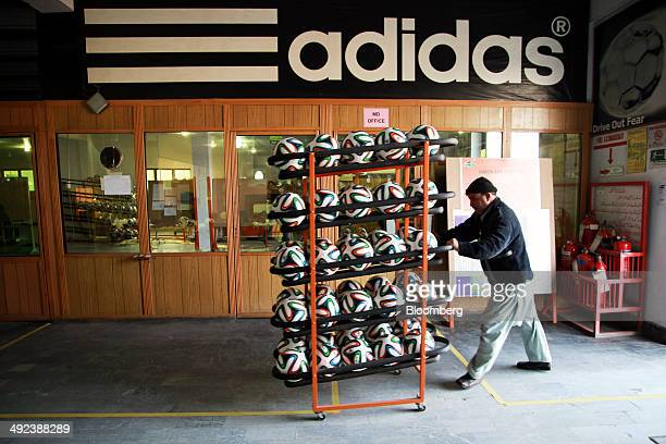 An employee transports a rack of Adidas AG 'Brazuca' soccer balls at the Forward Sports Ltd factory in Sialkot Punjab Pakistan on Tuesday Jan 28 2014...
