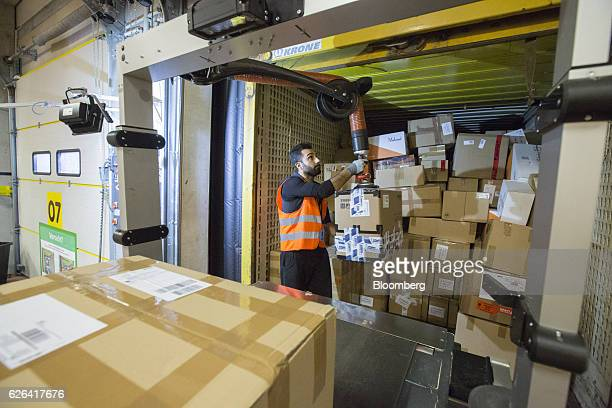 An employee transports boxes from a shipping container onto a conveyor at an Amazoncom Inc fulfillment center in Koblenz Germany on Tuesday Nov 29...